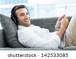 man on sofa with digital tablet  | Shutterstock . vector #142533085