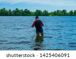 A fisherman with a small net is standing in the water. Fisherman checks the fishing net. Poacher uses the net in the bay - stock photo