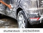 Small photo of Manual car wash in car wash shop service with employee worker in back.