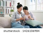 Small photo of Two joyful young excited asian women friends having fun point on mobile phone screen while sitting on comfortable sofa at home. Female friendship chatter funny pictures on cellphone pleasant memory