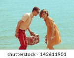 Couple walking on beach. Young happy married hipsters in trendy clothes playing and laughing on beach and holding vintage suitcase. Sunny summer day. Outdoor shot - stock photo
