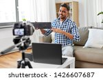 Small photo of blogging, videoblog and people concept - indian male blogger with camera recording video review of computer keyboard and making so-so gesture at home