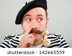 Small photo of Conceptual image of a French garlic seller picking his nose with his inger. He is wearing a blue coloured beret, and has a chain or necklace of garlic bulbs around his neck