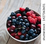 bowl filled with berries on on...   Shutterstock . vector #1427363651