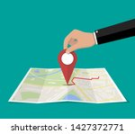 location pin in hand and paper... | Shutterstock .eps vector #1427372771