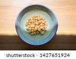 Small photo of Chickpeas soaked in bowl with water before cooking to shorten cooking time, wooden table background