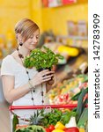woman smelling a potted fresh...   Shutterstock . vector #142783909