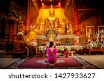 Small photo of Chiangmai, Thailand- June 3, 2019 : Asia woman wearing traditional dress of Thailand Pay respect to big golden buddha statute in the Silver temple Sanctuary Wat Srisuphan Chiangmai. Worship pray