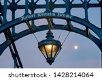"""enlightened lantern hangs in an arch of the historic bridge """"Kaiser Wilhelm Brücke"""" (= emperor william bridge) built in 1907 next to the moon in front of blue dawn sky, the name is written on it"""