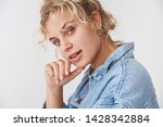 Small photo of Stylish attractive sassy blond blue eyed young 20s woman wearing denim jacket turning cheeky flirty camera touch chin give smug smirking delighted have interesting plan, standing white background