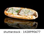 Philly cheese steak baguette with reflection isolated on black background. Studio Shot