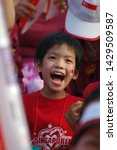 Small photo of Kallang, Singapore / Singapore - August 9, 2006 : A little boy with Singapore's national flag on his cheek in his red t-shirt smiling and cheering up with joy on Singapore National Day in 2006.