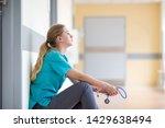 Tired female nurse in hospital corridor - stock photo