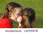 Two girls telling secrets outdoors at the park - stock photo