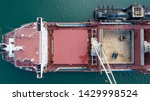 Small photo of Cranes working on cargo ship transporting sugar, Aerial pullback viewing work from above