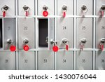Rows of metal lockers with numbered keys with red tags for storing valuables and personal possessions in a full frame view