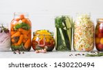 Small photo of Pickled vegetables. Salting various vegetables in glass jars for long-term storage. Preserves vegetables in glass jars. Variety fermented green vegetables on table.