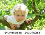 Smiling Child Climbing A Tree...