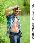 Small photo of Guy bearded cowboy in nature. Macho six packs torso wear rustic style clothes and cowboy hat. Strong and confident cowboy. Owner of rancho. Man unshaven face muscular torso cowboy. Farm concept.