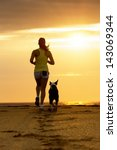 Stock photo woman and dog running toward the sun on summer beach in a beautiful golden sunset sport girl and 143069344