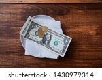 Small photo of Restaurant tips or gratuity. Banknotes and coins on a plate