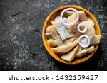 Stock photo pieces of salted herring in a plate with onion rings on dark rustic background 1432159427