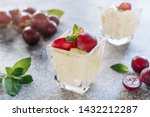 Small photo of Panakota Sweet Grape Dessert Classic Refreshment. Delicious Vanilla Cooked Cream Yogurt with Fruit Thickened with Gelatin and Molded Decorated Vine Green Leaves. Jelly Panna Cotta Closeup Photo