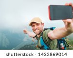 Young backpacker man taking selfie picture using smartphone and showing Thumbs Up during walking by the foggy cloudy weather mountain range .  Active sport backpacking healthy lifestyle concept.  - stock photo
