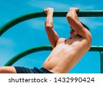 Small photo of Young adult fitness man preparing to do pull ups in pull up bar