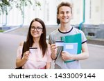 Small photo of Young students near university with books, exercise books holding credit cards and smiling to camera. Modern college learners using cards for online banking, buying things online, receiving stipend