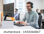 Small photo of Smiling handsome male customer support phone operator with headset working in call centre. Group of sales agent working in office.