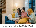 Group of Asian women couple play games at home, female using joystick having funny moment together on sofa in living room in night. Teenager young friend football fan, celebrate holiday concept.