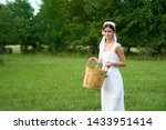Woman In White Dress Holding...