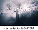 Demonic female figure in the fog, monochromatic shot - stock photo