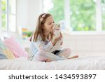 Stock photo child playing with baby cat on bed in white bedroom kid holding white kitten little girl in 1434593897