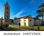 Man with bicycle near Church of St Anselm, Parish Church in town of Nin, Croatia