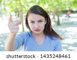 Small photo of Serious pretty young woman accusing viewer in park. Beautiful lady looking and pointing at camera with blurred green trees in background. Accusation concept. Front view.