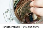 hand pulls bill from the jar.... | Shutterstock . vector #1435555091