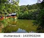 The Kumatakasha Spirit house close to Shin-ike pond in the Fushimi Inari Shrine in Kyoto, Japan. Fushimi Inari Taisha is an important Shinto shrine in southern Kyoto. Lake with reflection on water.
