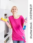 Happy housewife cleaning furniture at home. - stock photo
