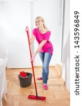 Happy woman cleaning and mopping floor at home. - stock photo