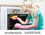 Young woman cleaning oven in the kitchen. - stock photo