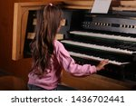 Little Girl Playing A Pipe Organ