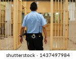 Jailer walking through the prison aisle, entering the safe zone. Prison officer in  blue shirt with handcuffs and a baton bypassing the corridor of a jail.