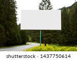 Small photo of Outdoor image of blank huge billboard standing near road on way to mountains, having many evergreen trees around, sides of green divided by paved road, amazing landscape. Copyspace for advertisement.