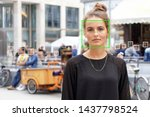 young woman picked out by face detection or facial recognition software - several other faces detected in crowd of people in background