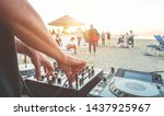 Small photo of Dj mixing at sunset beach party in summer vacation outdoor - Disc jockey hands playing music for tourist people in chiringuito kiosk bar - Event, music and fun concept - Focus on right hand