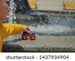 Stock photo boy playing with plastic colorful bigfoot toy car hold it in hand 1437934904
