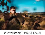 Hunter with shotgun gun on hunt. Process of duck hunting. Hunter with a shotgun in a traditional shooting clothing
