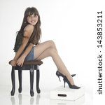 Teen Girl Posing In Heels Sitting Down Against a White studio background - stock photo